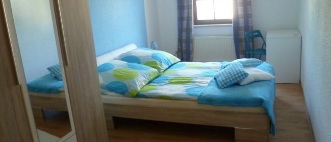 Ein großes Doppelbett sowie ein kleiner Schreibtisch bieten Rückzugsmöglichkeiten.