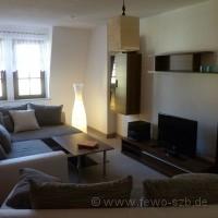 Im 18 m² großen Wohnzimmer steht eine Couchlandschaft mit Aufbettungsmöglichkeit.